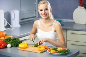 Young happy woman making salad at domestic kitchen