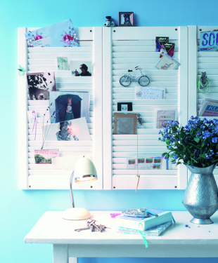 Weisse Lamellenschranktueren als Memobord und ein Tisch als Ablage