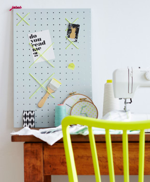 Werkzeuglochwand als Memoboard mit neonfarbenen Gummibaendern, Tool hole wall as a memo board with neon-colored rubber bands,